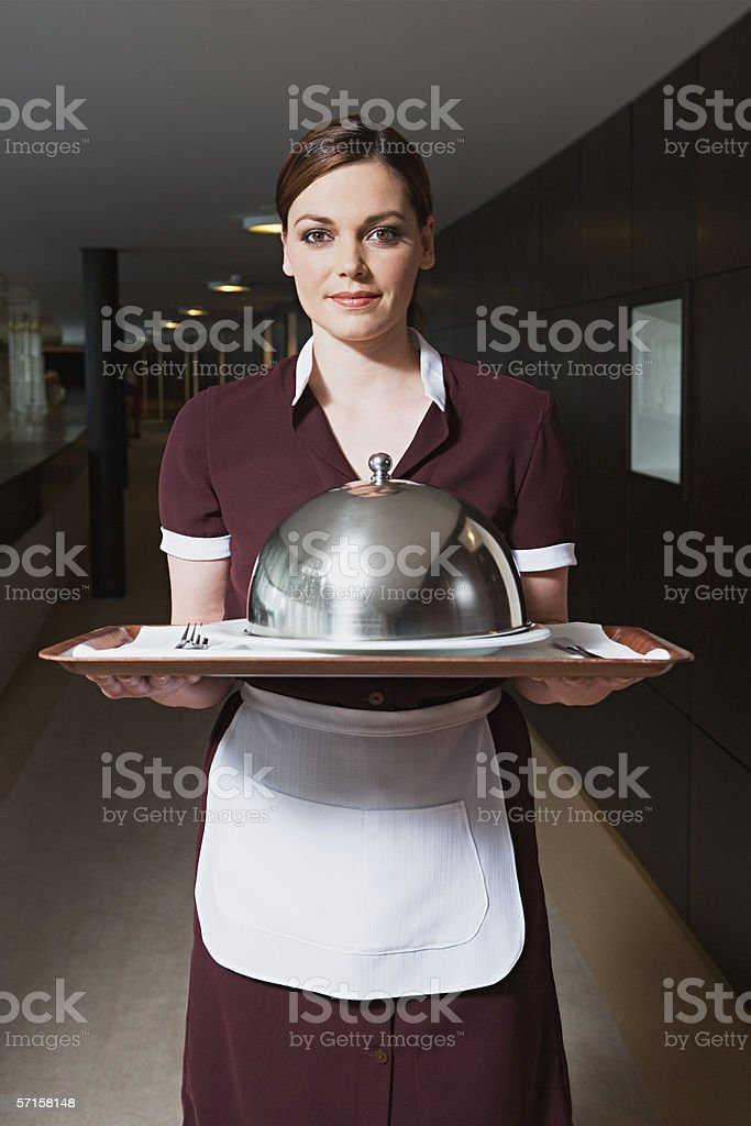 Maid carrying tray stock photo