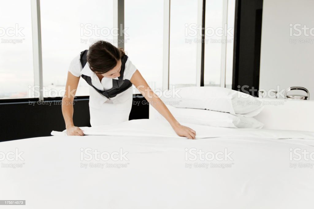 Maid Changing Sheets in a Hotel Room royalty-free stock photo