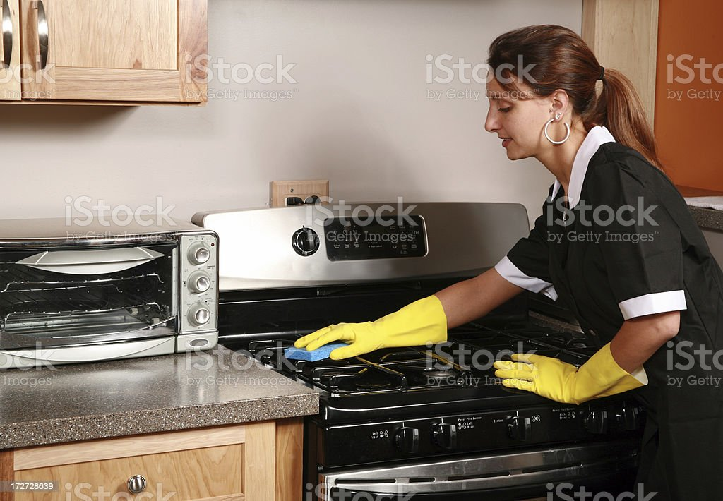 Maid Cleaning A Stove stock photo