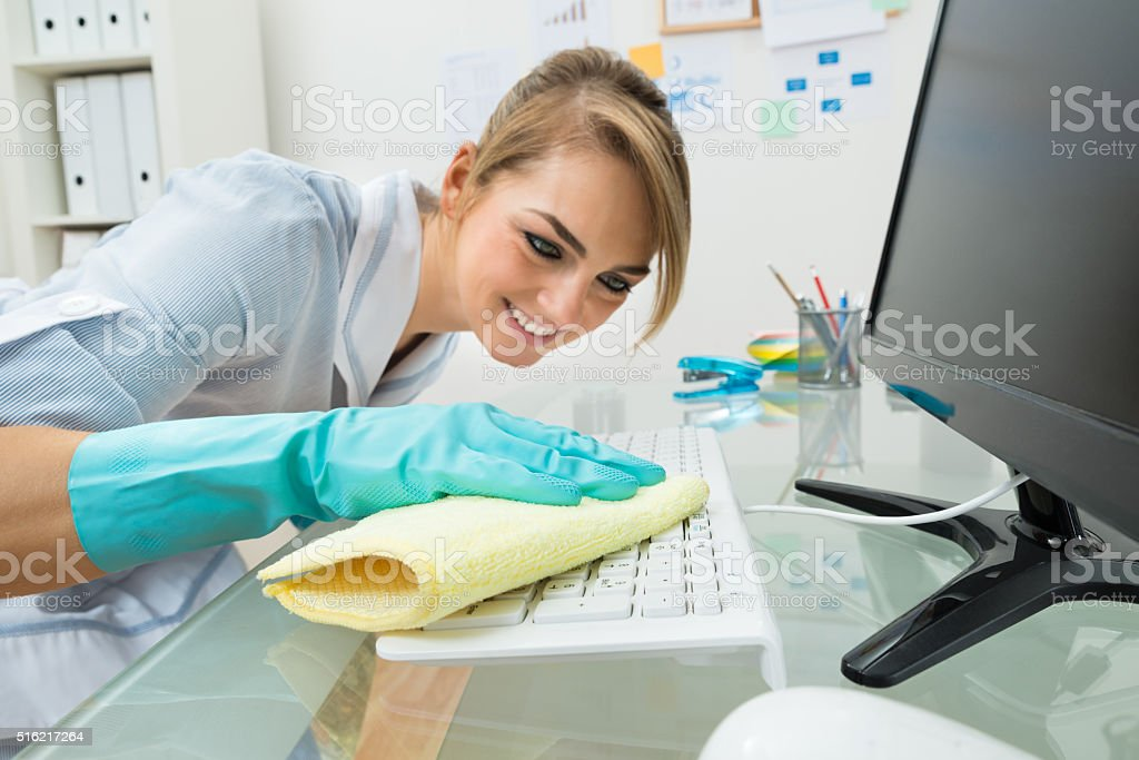 Maid Cleaning Keyboard At Desk stock photo