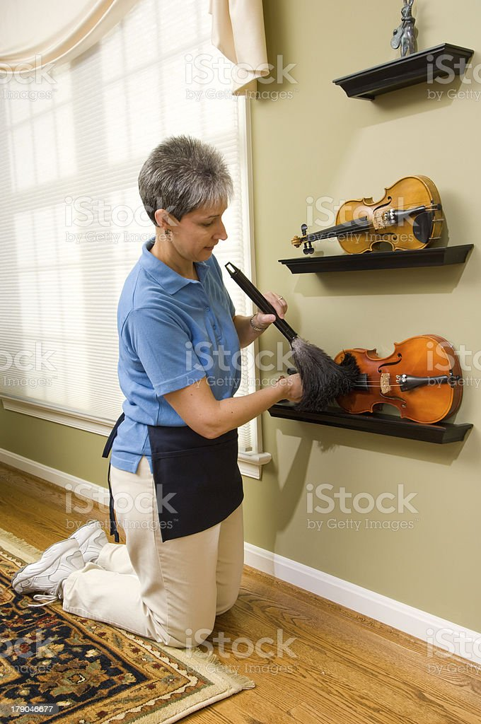 Maid Dusting Violins on Display royalty-free stock photo