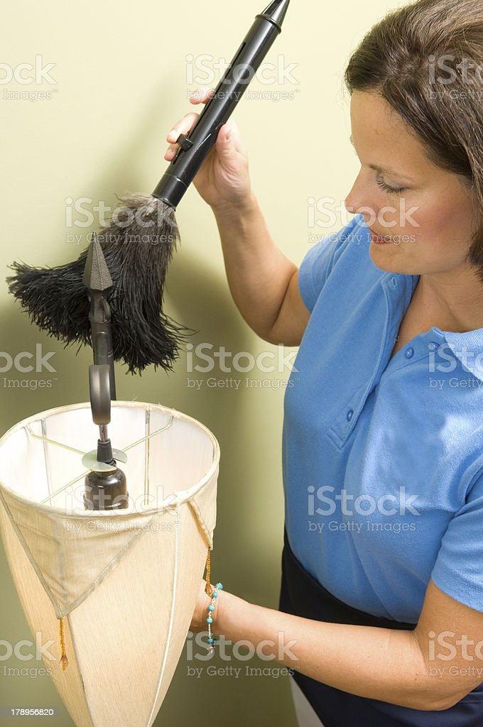 Maid Feather Dusting a Lamp royalty-free stock photo