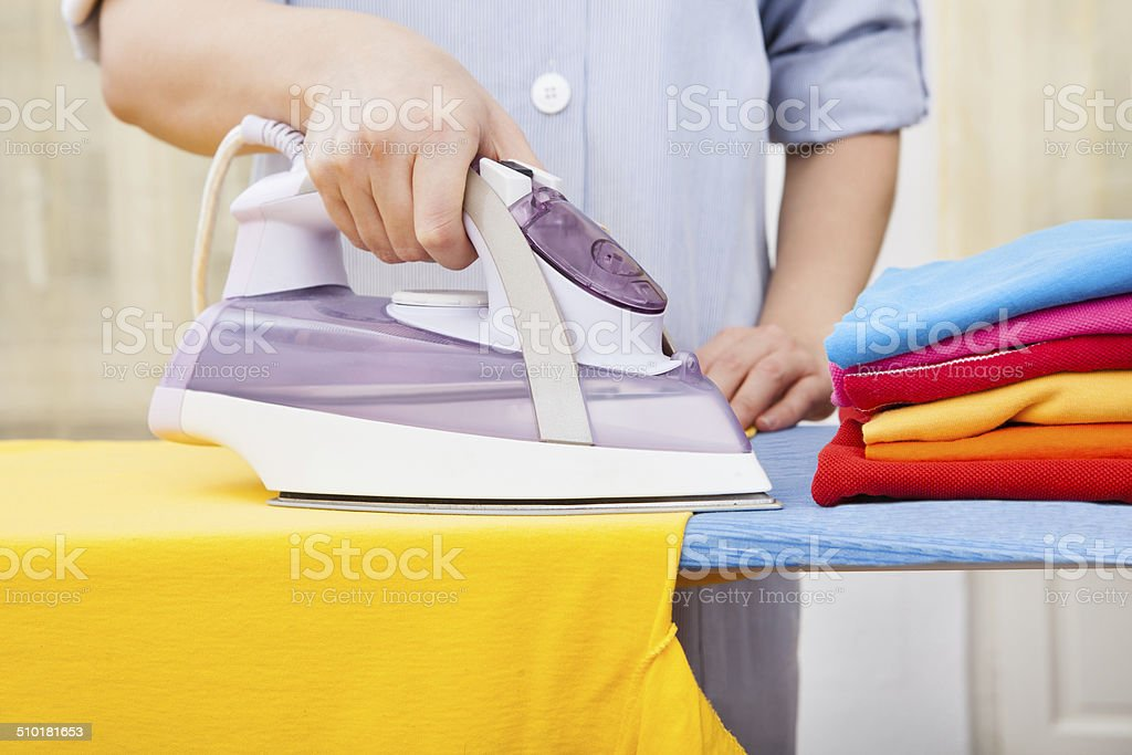Maid Ironing Clothes stock photo