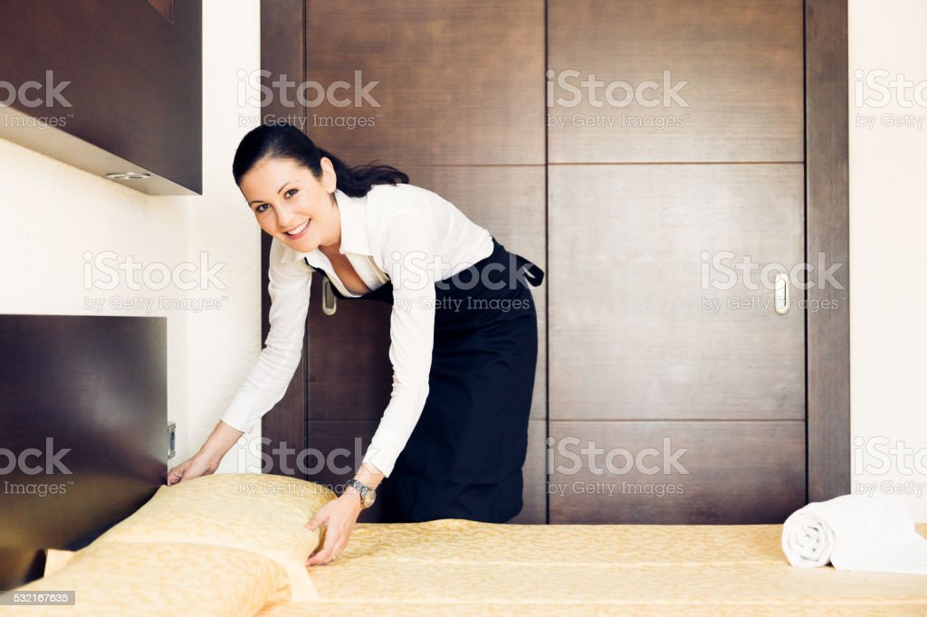 maid making a hotel room stock photo