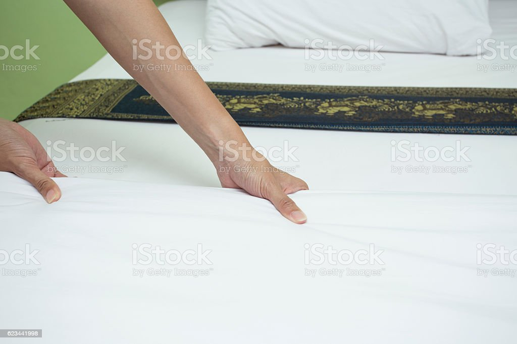 Maid making bed in hotel room, close up stock photo