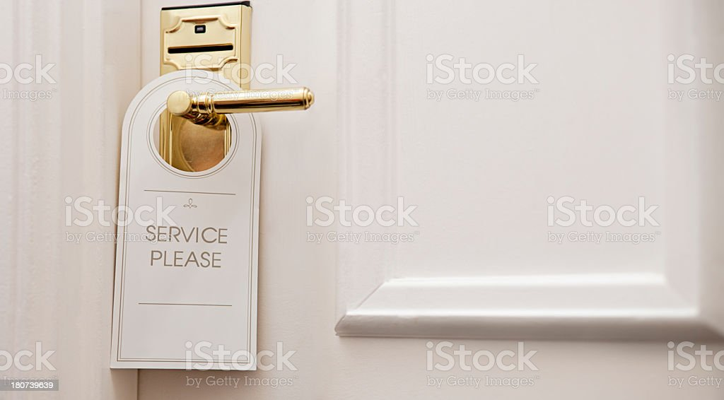 Maid service hanger on hotel door knob stock photo