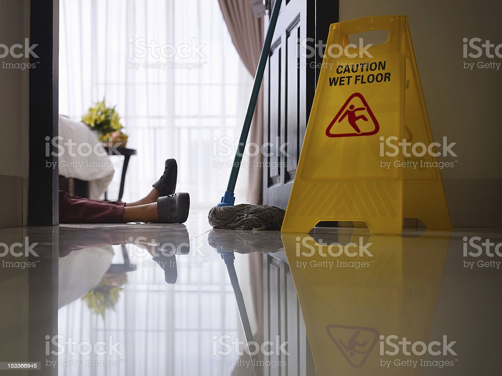 maid slipped on wet floor and laying down stock photo