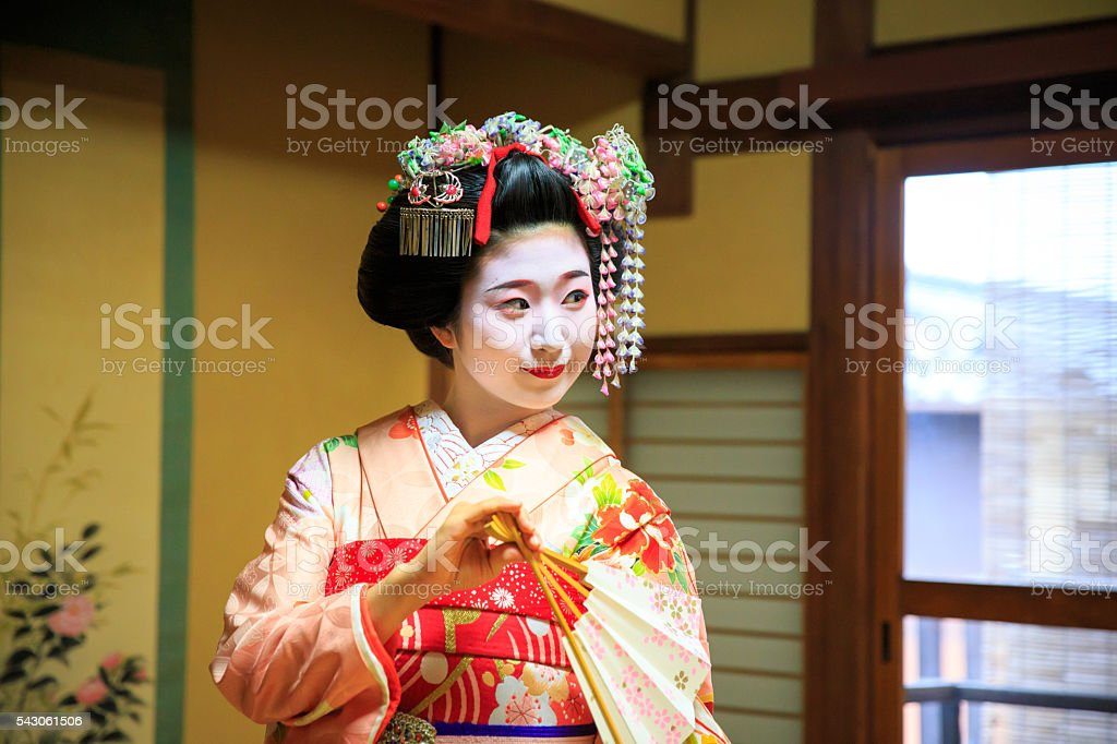 Maiko girl dancing with paper fan in tatami room stock photo