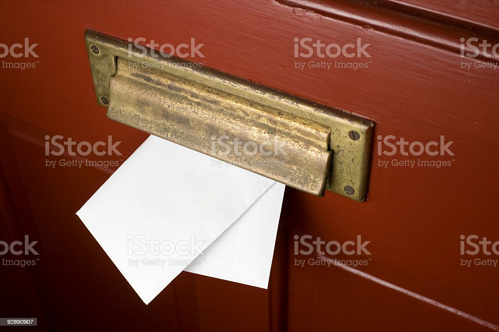 Mail going through a mail slot on a red door stock photo