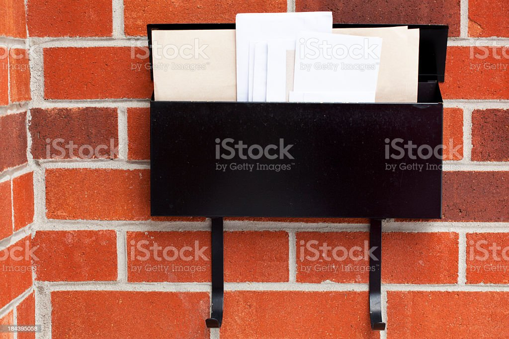 Mail in an open black mailbox on a red brick wall stock photo
