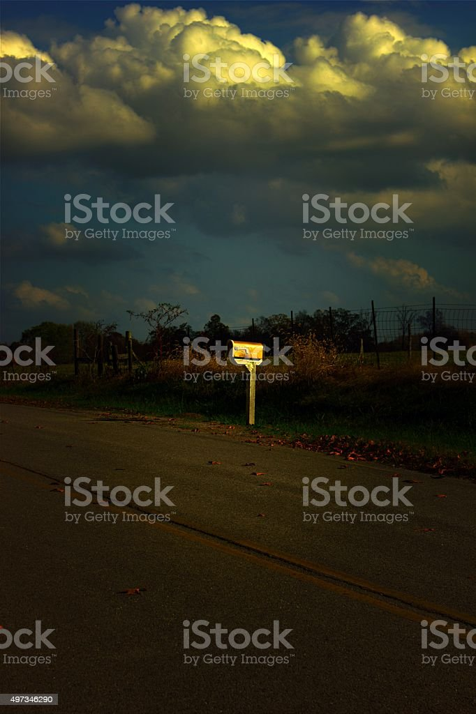Mailbox Beside Highway at Sunset with Dramatic Clouds, Autumn Leaves stock photo