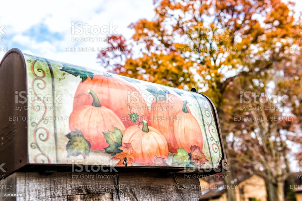 Mailbox in autumn Virginia neighborhood with pumpkin decoration and golden foliage on trees stock photo