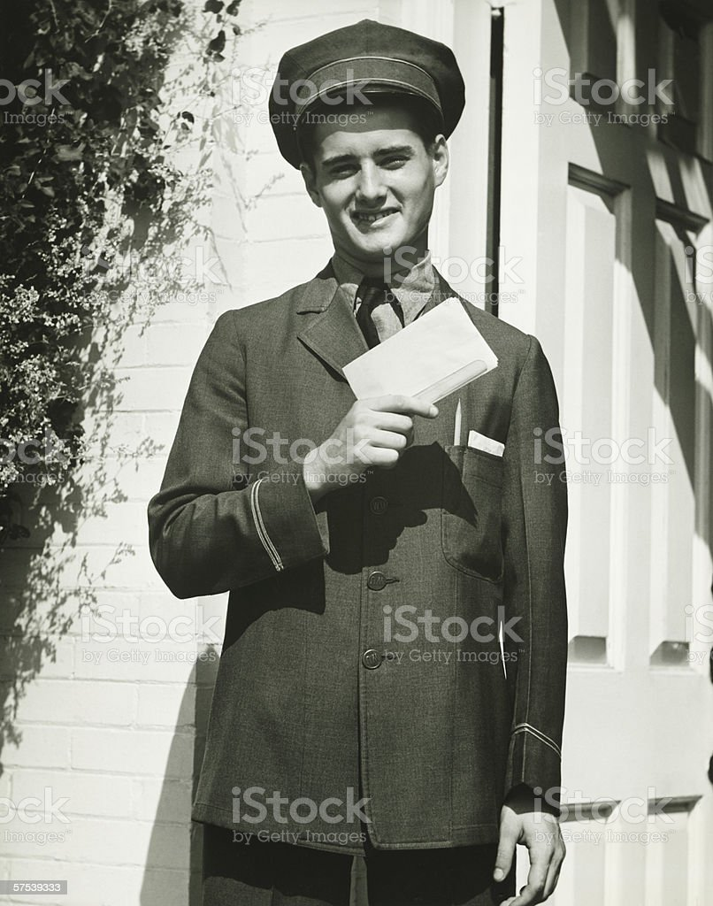Mailman holding blank form outdoors, (B&W), portrait stock photo