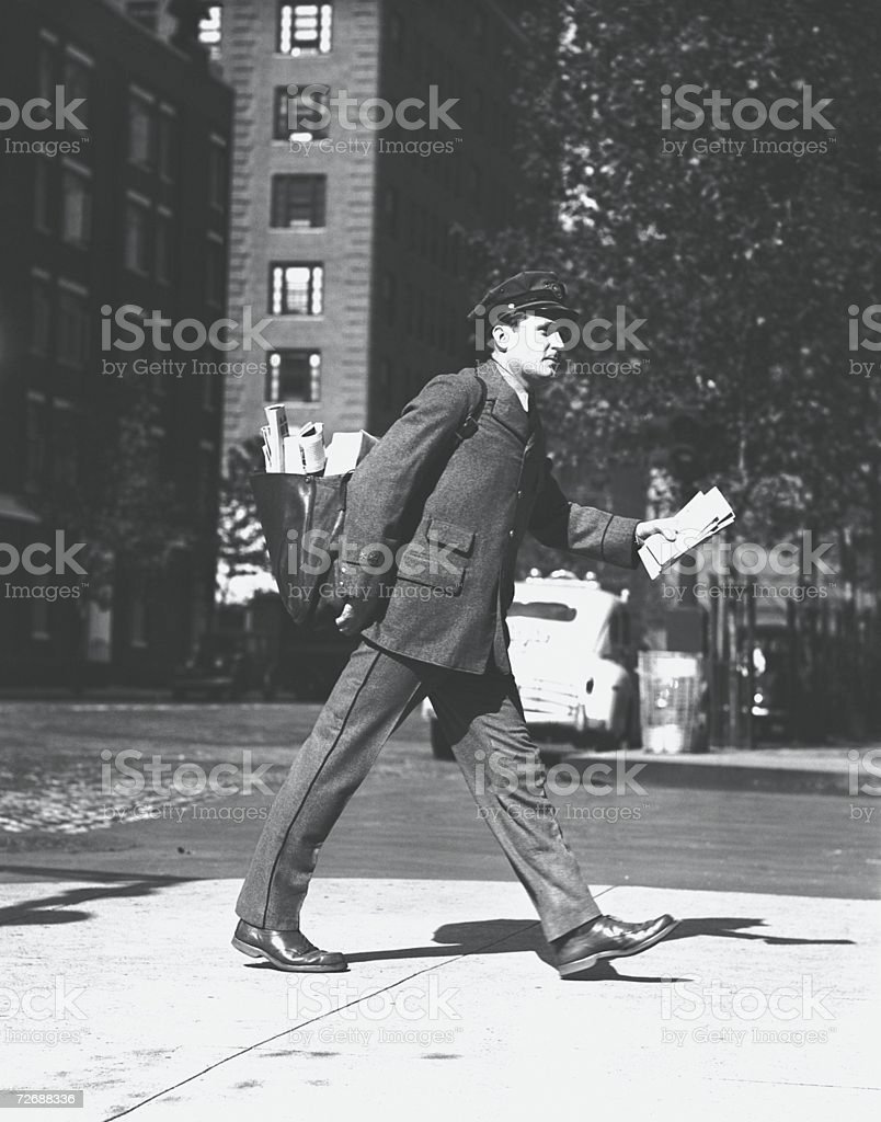 Mailman holding letters walking on street, (B&W) stock photo