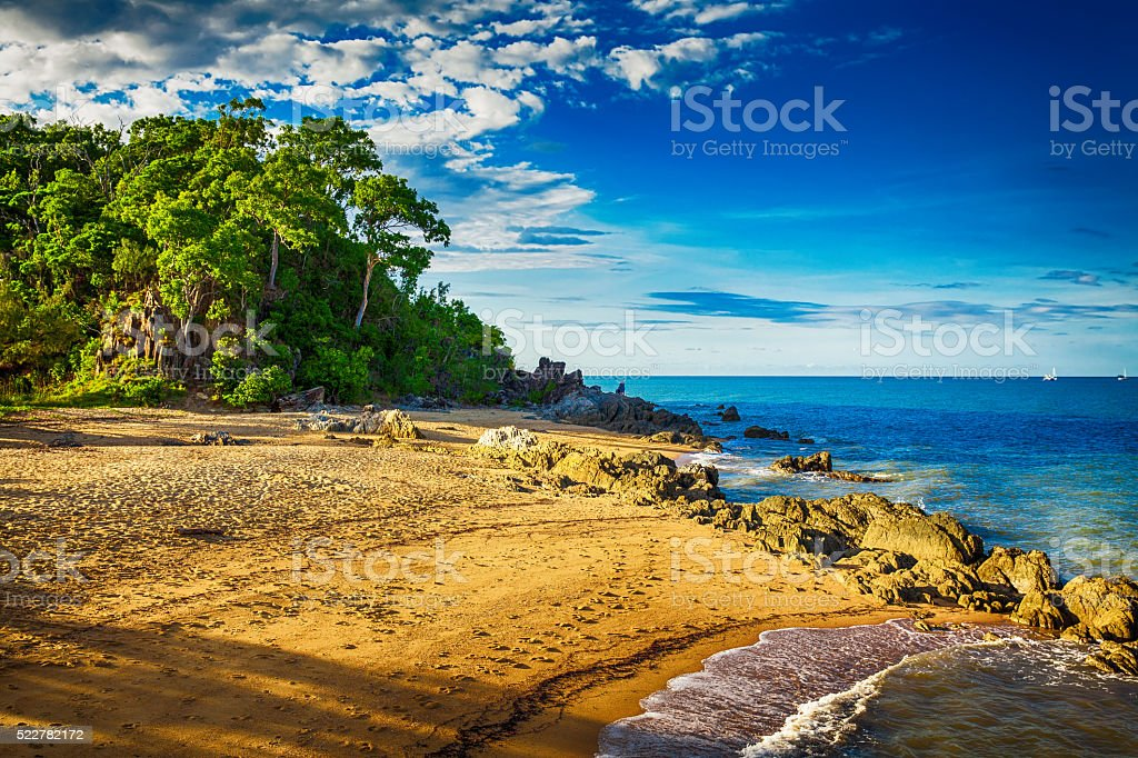 Main beach in Palm cove with rocks during sunset stock photo