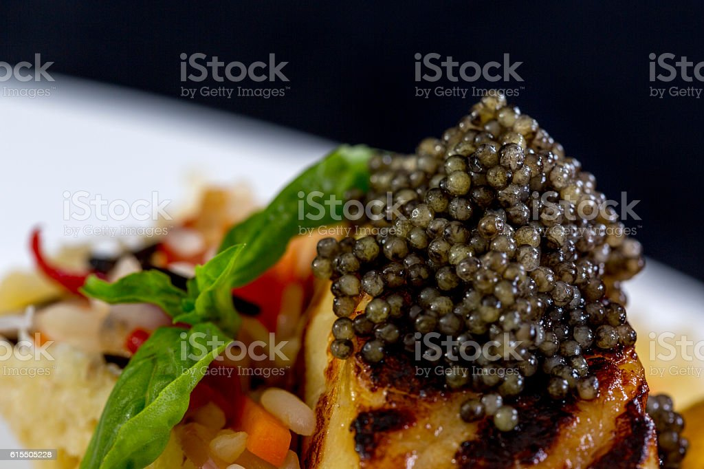 Main course in restaurant. Grilled fish with black caviar stock photo