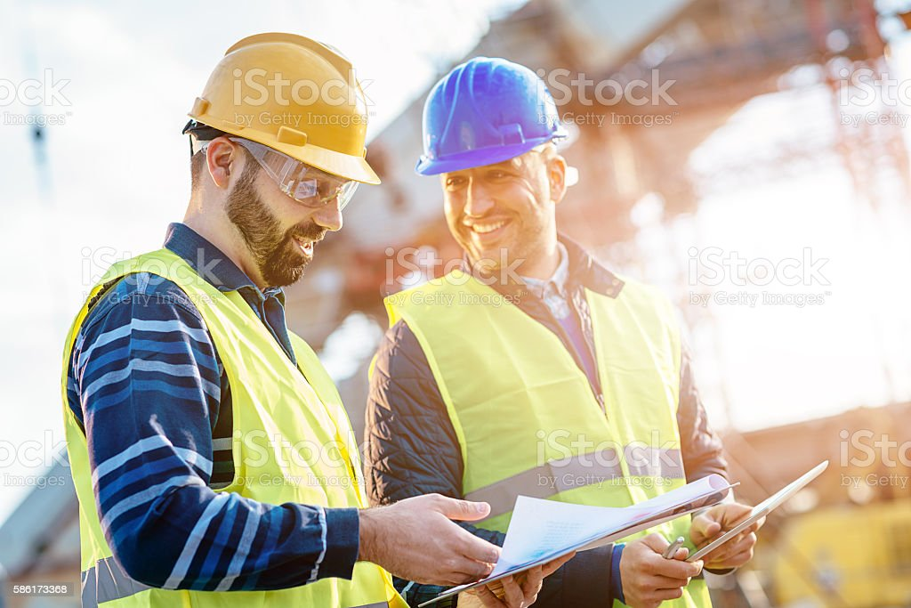 Main engineer showing report to contractor at construction site stock photo