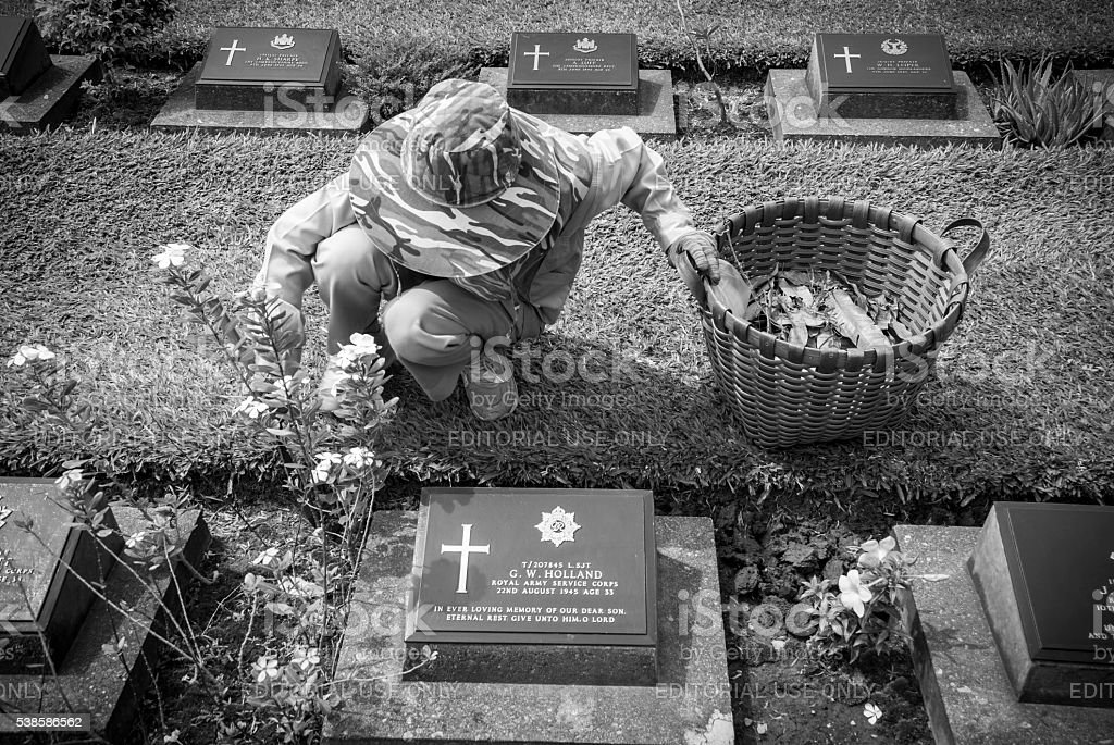 Maintaining WWII cemetery in Kanchanaburi, Thailand stock photo