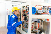 Maintenance engineer in factory, controling the machine