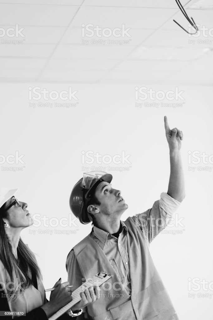 Maintenance engineers checking cables for fire alarm stock photo