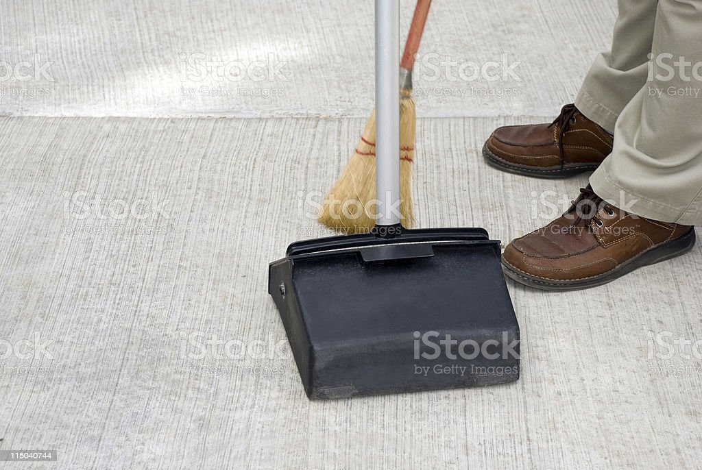 Maintenance Person Sweeping with Broom Into a Commercial Dust Pan royalty-free stock photo