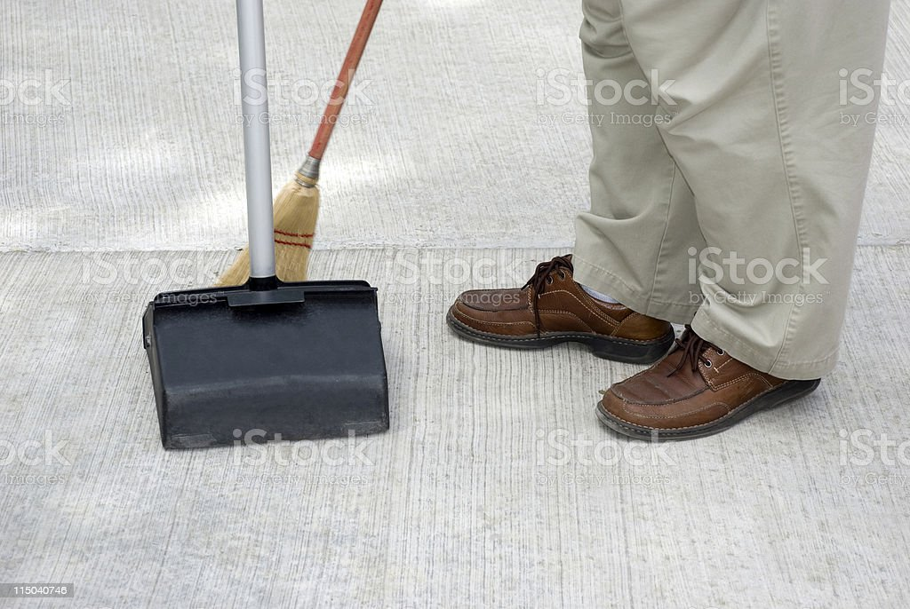 Maintenance Person Sweeping with Broom Into a Commercial Dustpan royalty-free stock photo