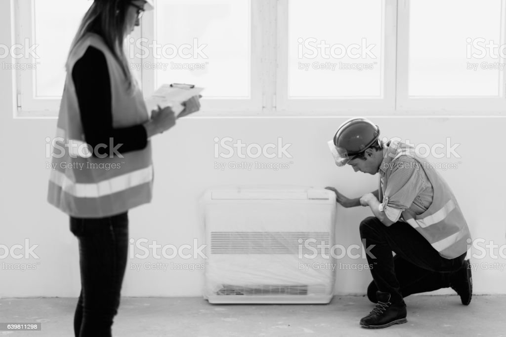 Maintenance technicians checking air conditioning units stock photo