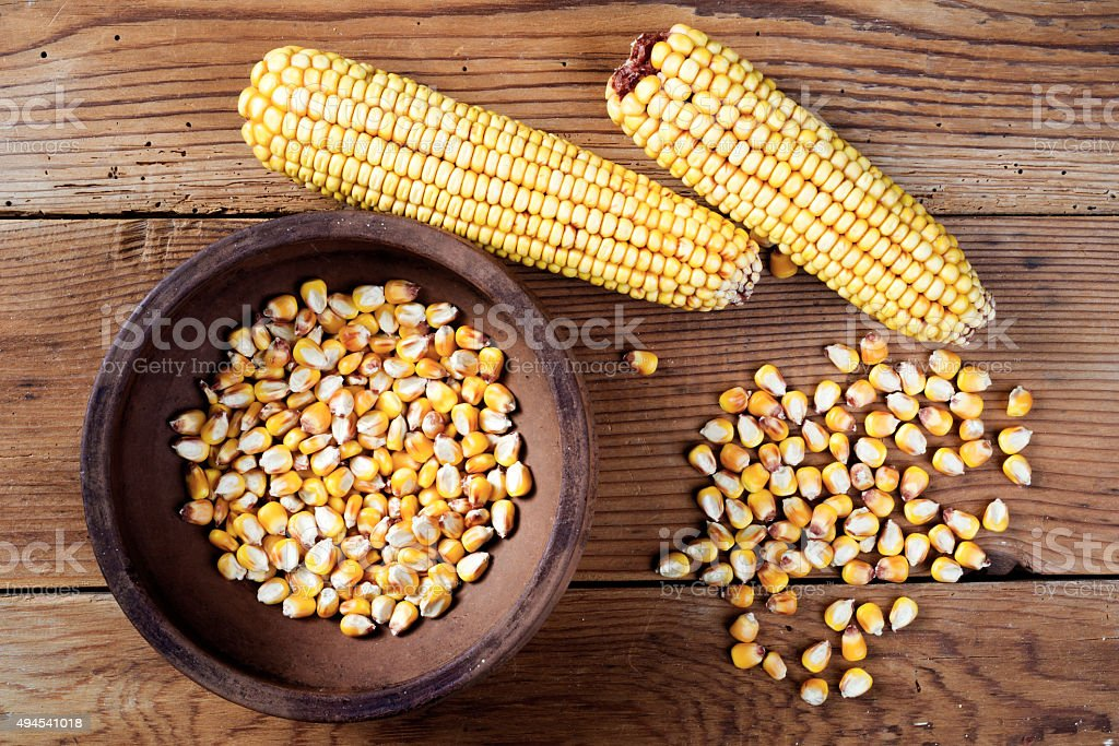 Maize and ceramic bowl on wooden table stock photo