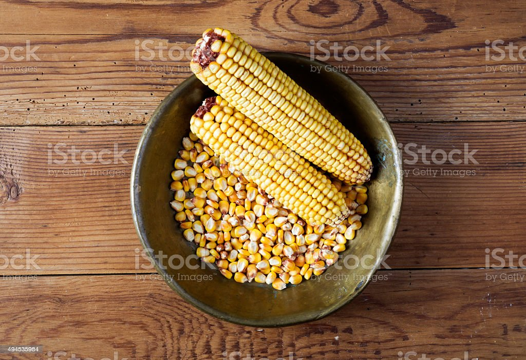 Maize in copper tray on wooden table stock photo