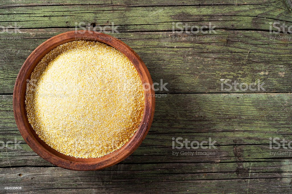 Maize  meal and ceramic bowl on wooden table stock photo