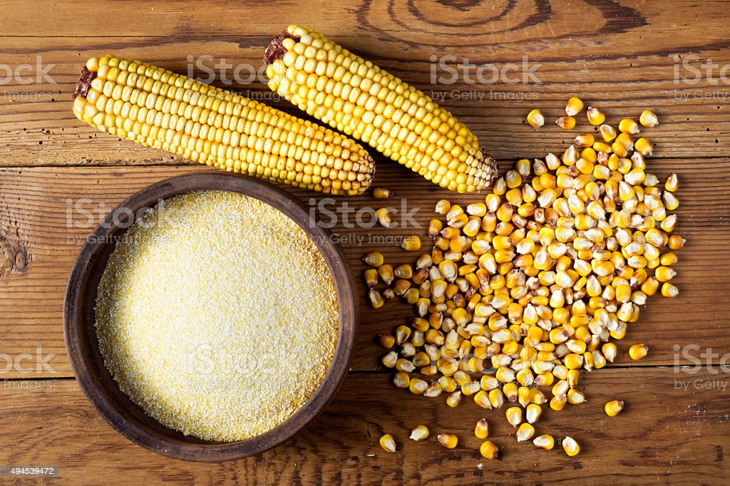 Maize, meal and ceramic bowl on wooden table stock photo