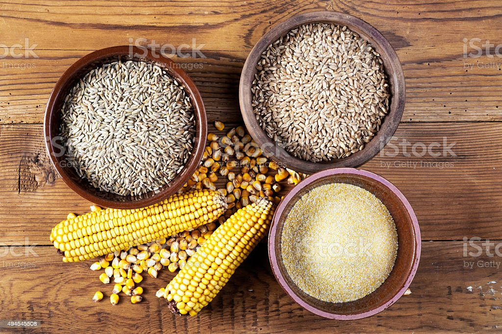 Maize, wheat, rye, meal and ceramic bowls on wooden table stock photo