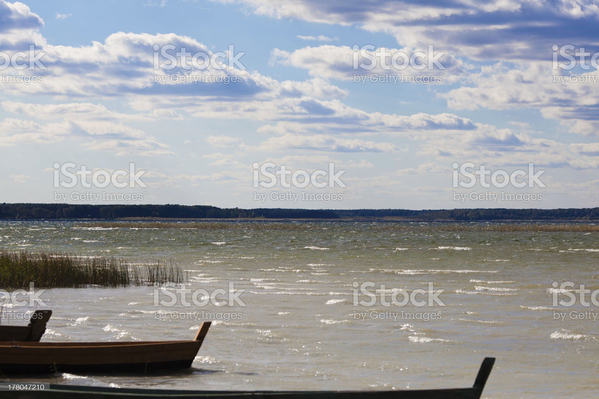 Majestic cloudscape and stationary boats at lakeside royalty-free stock photo