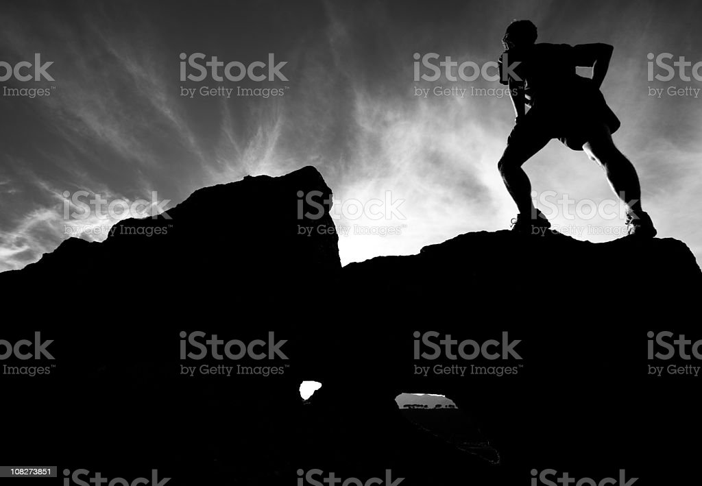 Majestic silhouette of a runner on rock outcropping royalty-free stock photo