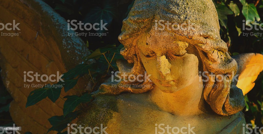 Majestic view of statue of golden angel in sunlight against stock photo