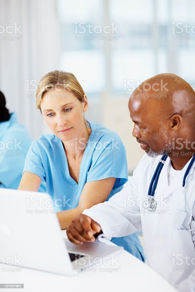 Make and female doctor working on a white laptop royalty-free stock photo