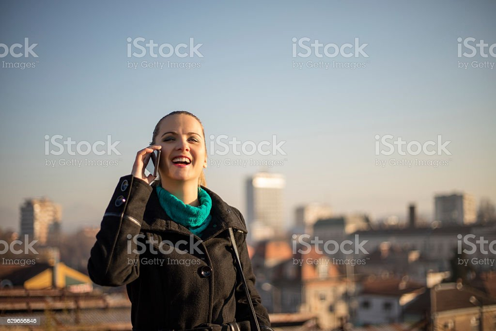 Make call with smartphone, on the hill over a city. stock photo