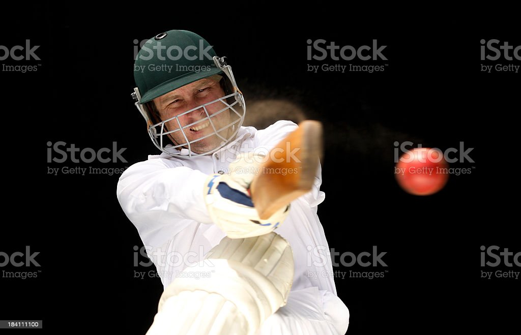 Make cricket player executing shot on red ball against black stock photo