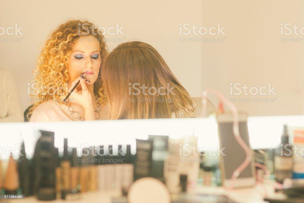 Make up artist applying cosmetics in makeup studio stock photo