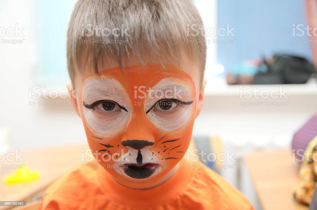 Make up artist making tiger mask for child stock photo