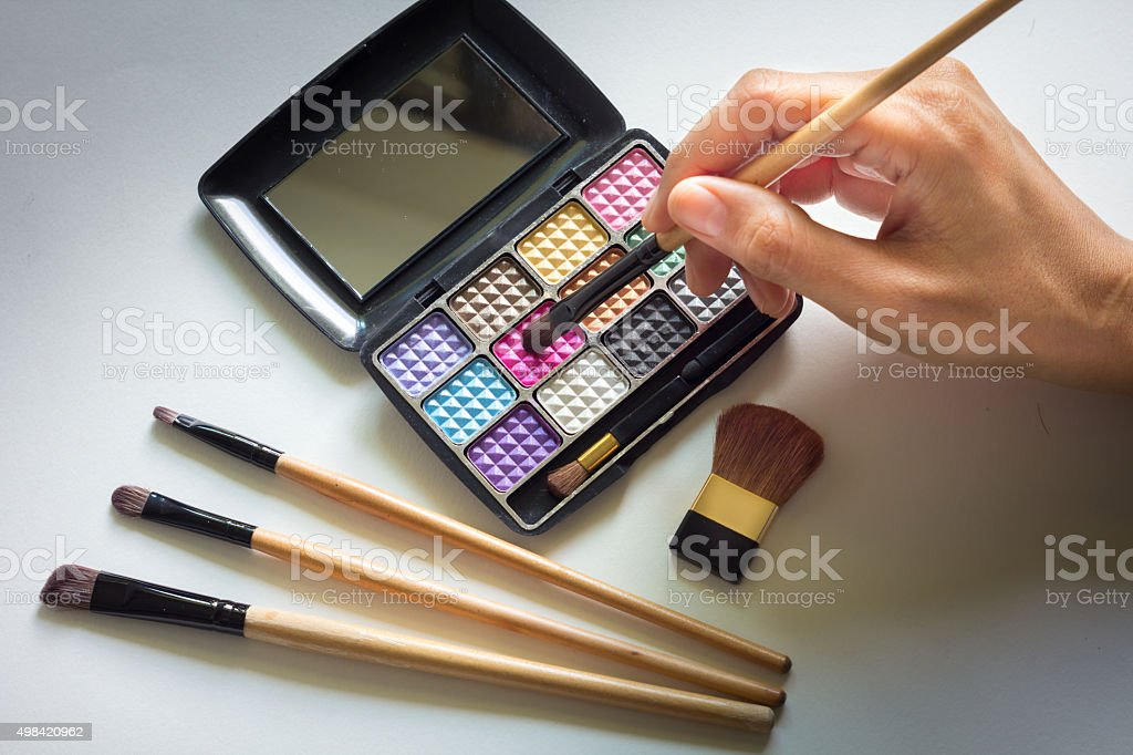 Make up brush in hand with cosmetic. stock photo