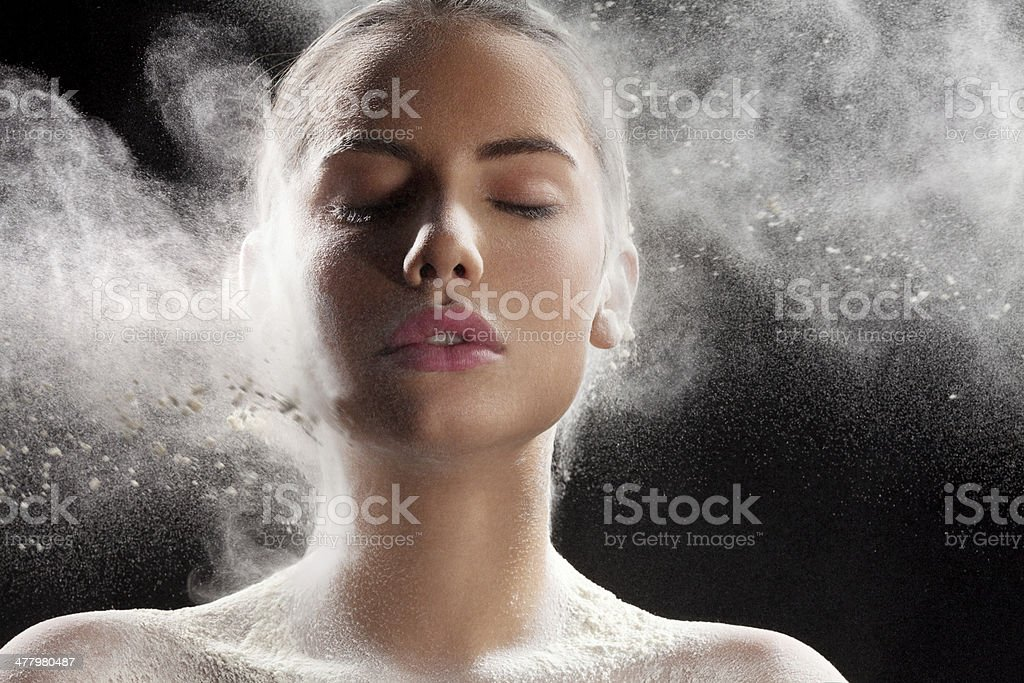 Make up powder splashing on the face stock photo