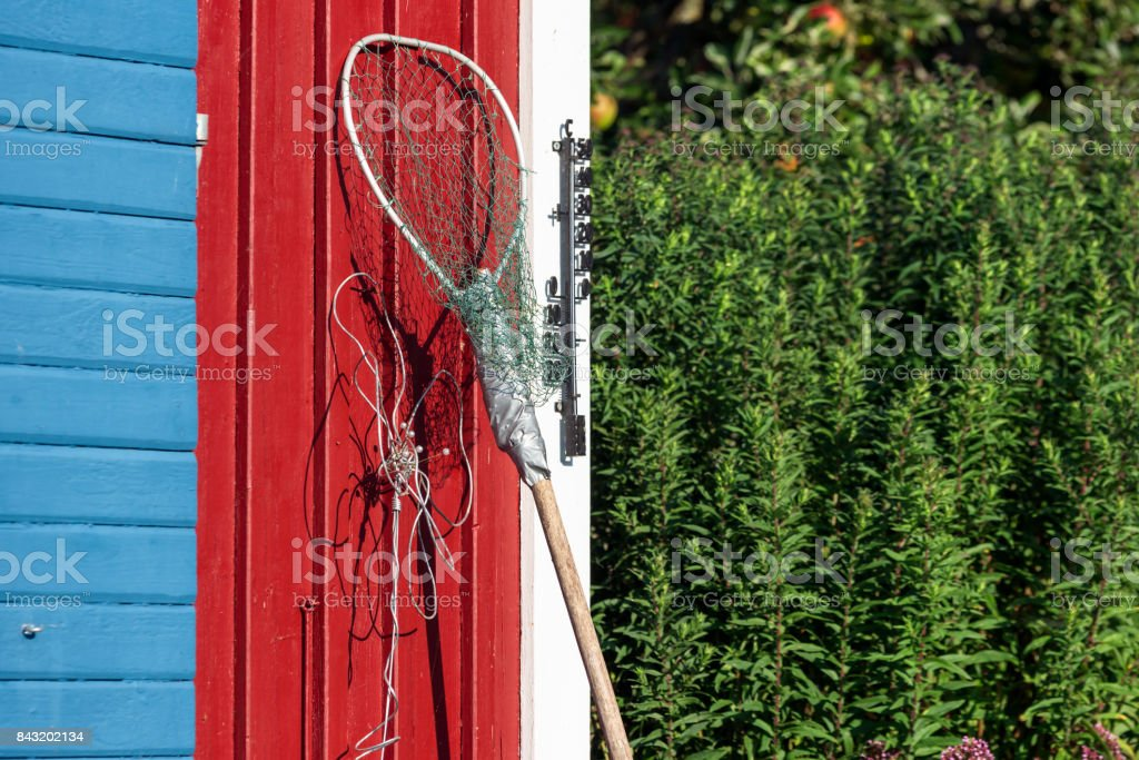 Makeshift landing net leaning against wall stock photo