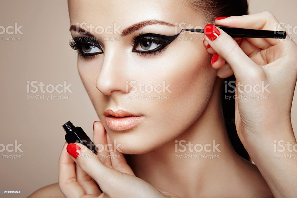 Makeup artist applies eye shadow stock photo