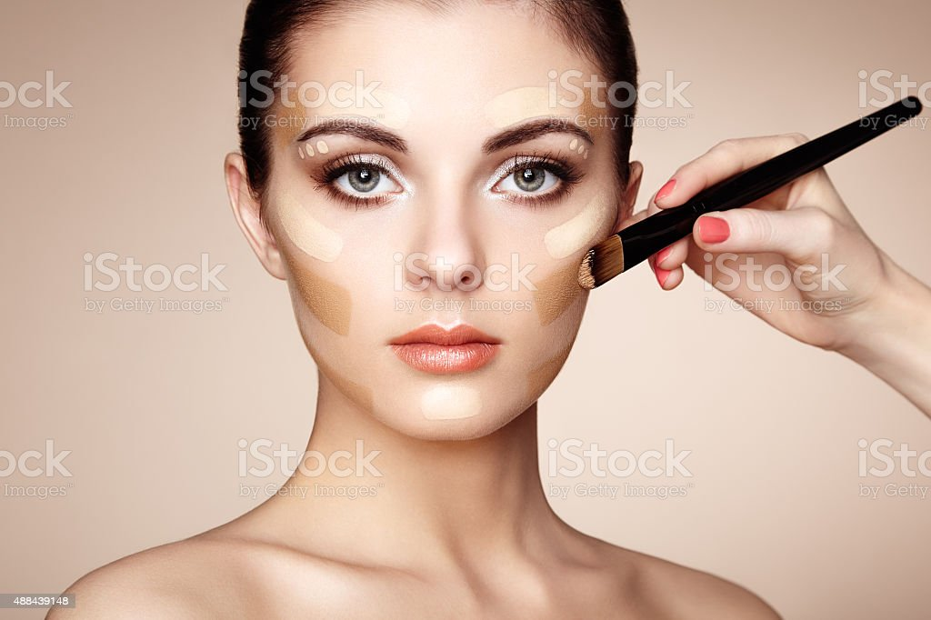 Makeup artist applies skintone stock photo