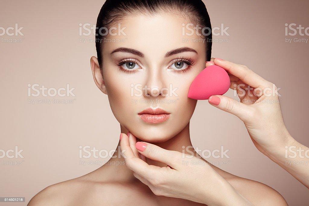 Makeup artist applies skintone stock photo
