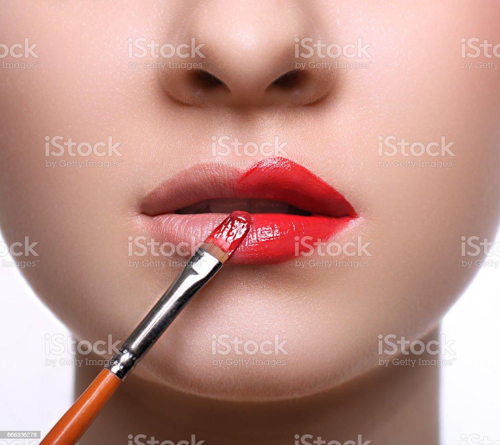 Make-up artist apply lipstick with brush, beauty stock photo