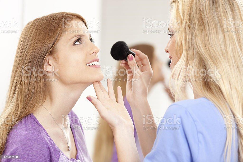 Makeup artist applying blush to young women. royalty-free stock photo