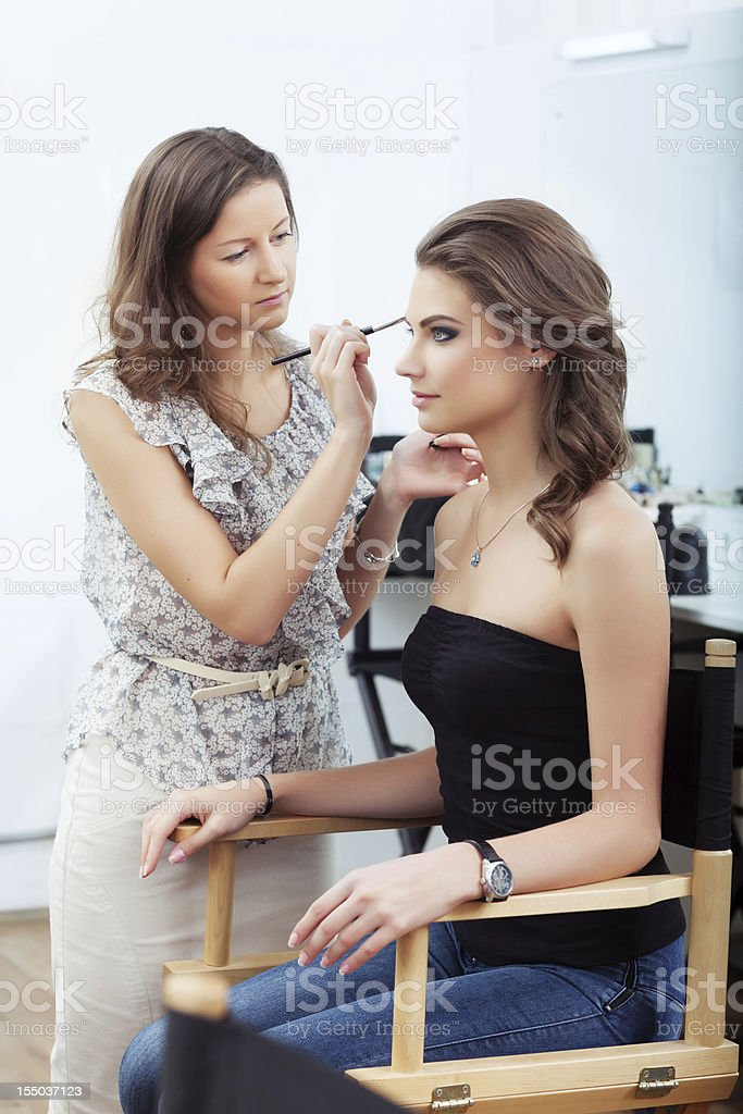 Makeup artist applying eyebrow makeup on woman royalty-free stock photo