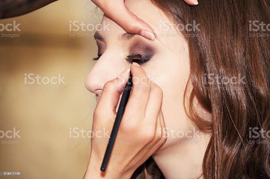 Makeup artist applying eyeshadow stock photo